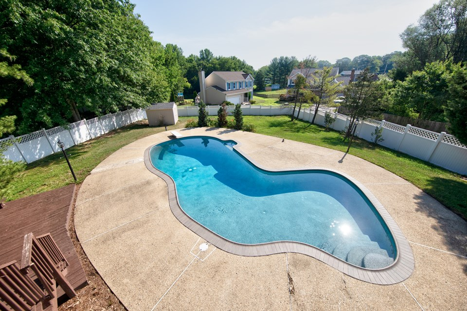 in ground concrete pool with patio