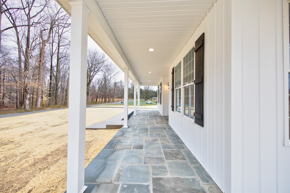 covered front porch with blue stone